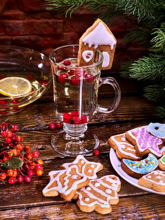 Christmas glass latte mug and Christmas multicolored cookies on plate with fir branches. Mag decoration cookie in form of house on wooden table in restaurant. Stock Photo