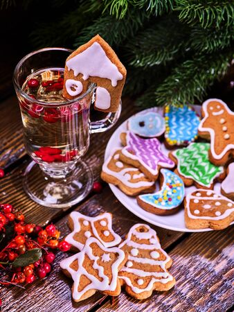 Christmas cookies on plate with fir branches. Christmas still life with mug hot drink with red berry on wooden table in restaurant.