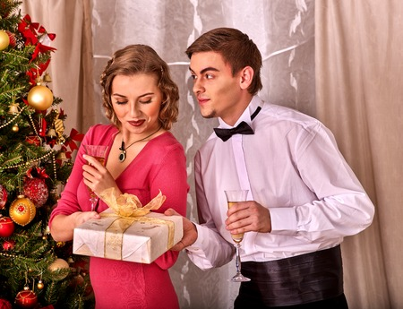 Couple on party near Christmas tree. Man gives a gift box woman with a Christmas surprise. Retro style.
