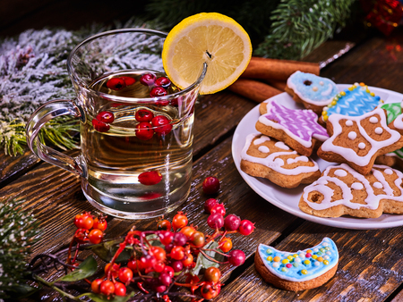 mag: Christmas glass mug and Christmas multicolored cookies on plate with fir branches. Mag decoration lemon slice on wooden table. Christmas treats.
