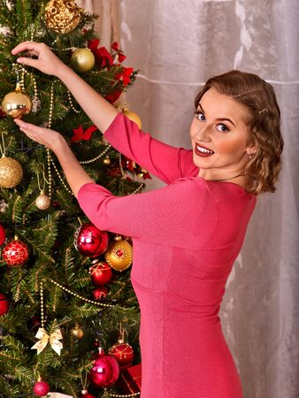 christmas tree ball: Woman dressing Christmas tree. Woman hangs up last Christmas ball on Christmas tree. She turns her face and looking at camera.