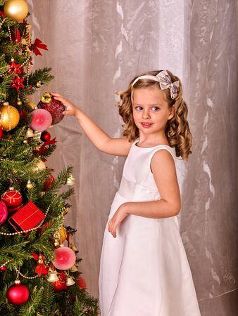 vistiendose: Niño en vestido blanco decorar el árbol de navidad. Chica es muy feliz. Muchacha que sostiene una bola roja de Navidad.