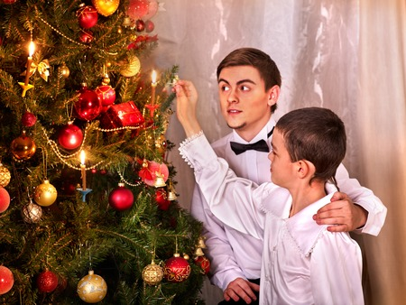 Father and son set fire to the candles on the Christmas tree. Happy Christmas Eve for the family. Retro style. Stock Photo