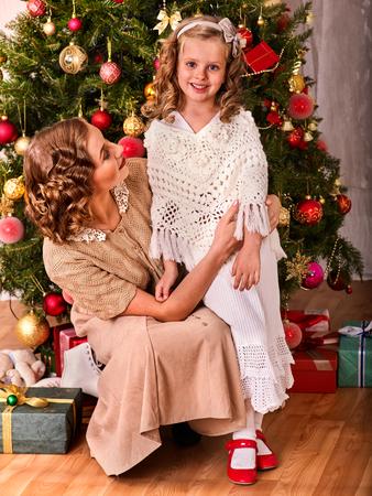 niños vistiendose: La madre abraza la hija en la mañana de Navidad. niña feliz en el fondo del árbol de Navidad. Familia feliz. Estilo retro.