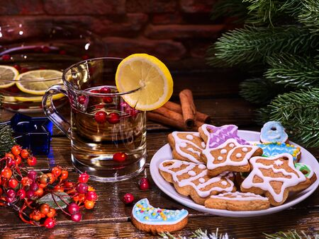 mag: Christmas treats. Christmas glass latte mug and Christmas multicolored cookies on plate with fir branches. Mag decoration lemon slice on wooden table in restaurant and cinnamon sticks. Stock Photo