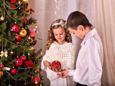 niños vistiendose: Los niños que reciben los regalos bajo el árbol de Navidad. El hermano y la hermana de decorar un árbol de Navidad. Familia feliz se prepara para celebrar la Navidad. Foto de archivo