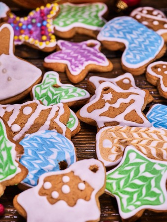 woden: Christmas background multicolored gingerbread cookies and cinnamon sticks on woden table .