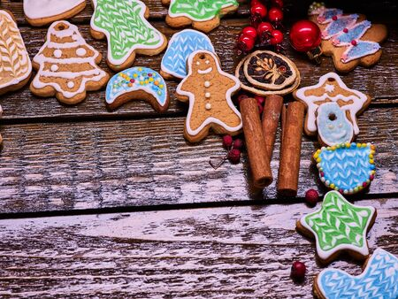 woden: Right-hand angle of Christmas gingerbread cookies and cinnamon sticks on woden table . Background with copy spice.
