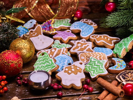 woden: Christmas gingerbread cookies on woden table and candels with Christmas ribbon.