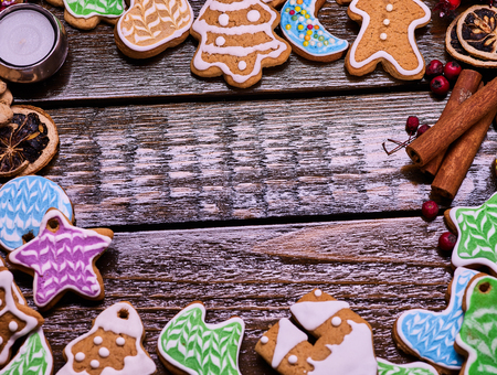 woden: Christmas gingerbread cookies on woden table and candels. Frame with ginger snap and cinnamon sticks. Wooden place for text or wishes.