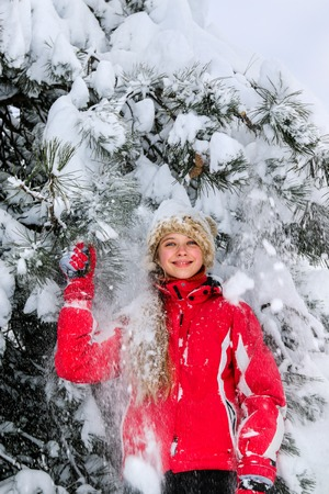 Teen girl laughs and stands against a background of snow-covered fir trees.
