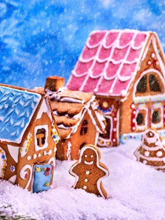 Straße, bestehend aus Lebkuchenhäuser mit Glasur. Lebkuchen-Mann geht auf einer schneebedeckten Straße. Lebkuchen-Weihnachtsbaum und Schneefall.