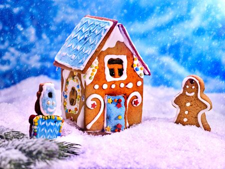 Beautiful gingerbread cookie house on a background of blue sky. Gingerbread man and snowman celebrate Christmas.