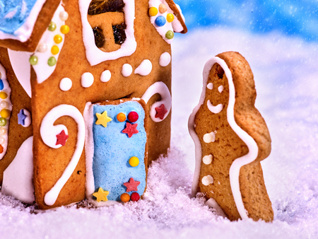 Gingerbread man side view, close-up. Gingerbread house standing in the snow, snowfall. Merry Christmas. Stock Photo