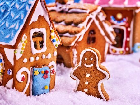 Street consisting of gingerbread houses, close-up. Joyful Gingerbread man in the snow. Merry Christmas. Stock Photo