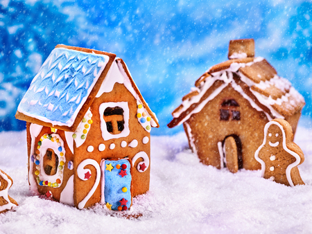 village man: Two gingerbread houses and gingerbread man next to them in the snow. Village Christmas gingerbread houses in the winter background.