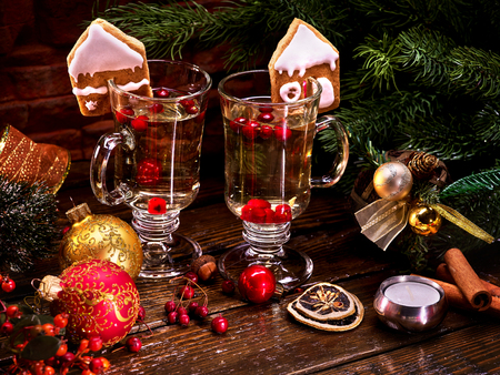 Beautiful Christmas still-life from two glasses of hot punch and surrounded by fir branches and Christmas balls. Stock Photo
