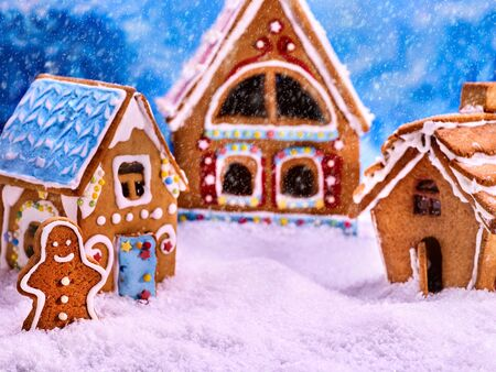 foreground: Three fabulous gingerbread house for Christmas. Gingerbread man winter foreground. Snowfall and Christmas. Food concept.
