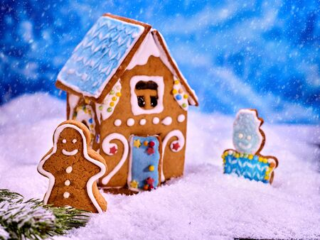 christmas cookie: Christmas cookie house with blue roof in snow on winter background. Gingerbread man and gingerbread cookie snowman next to gingerbread house.