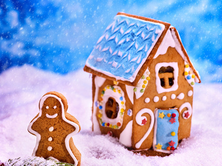 sugar cookie: Christmas gingerbread house cookie in sugar snow next to gingerbread man. Christmas food concept on sky blue background. Stock Photo