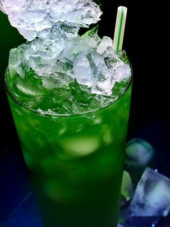vaso de precipitado: Coctel del alcohol en la barra. Cierre de cóctel de alcohol congelado sobre fondo negro. bebida mezclada con paja verde. Vista superior de aperetif.