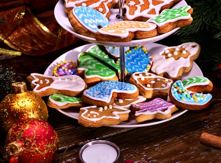 sweet course: Christmas Cookie of Gingerbread. Sweet course of confection on dessert stand. Two level of pastry. Xmas ball foreground. Candle on wooden table. Colourful biscuit on plate. Holiday food in restaraunt. Stock Photo