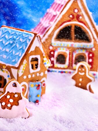 holiday house: Gingerbread man , house near tree Christmas cookie with blue sky and falling winter snow. Xmas food decoration is designed as sweets country lodge. It can be used as holiday cards. Stock Photo