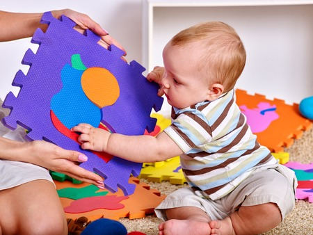 Family puzzle making mother and baby. Child jigsaw develops children. Mom holding big pieces helping kid. Boy and mothers hands close up. Playing on floor in kindergarten.