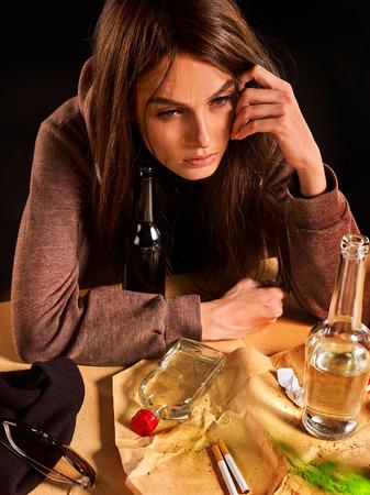 soledad: alcoholismo mujer es un problema social. consumo femenino de alcohol es la causa de la soledad. Ella beber alcohol en el estado de ánimo depresivo. Desorden en la mesa chica borracha, porque en el fondo negro.