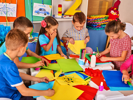Child cutting paper in class. Kids development and social lerning children in school. Childrens project in kindergarten. Pictures into background. Reklamní fotografie - 69480630