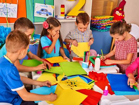 Papel de corte de criança em classe. Desenvolvimento de crianças e educação social das crianças na escola. Projeto infantil no jardim de infância. Imagens no fundo. Foto de archivo