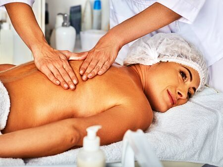 Massage woman therapist making manual therapy back. Hands of masseuse close up. Treatment of spinal injuries 40 old client in spa salon. Stock Photo