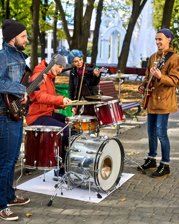 street musician: Festival music band. Friends playing on percussion instruments in city park. Fountain and trees in the background. Stock Photo