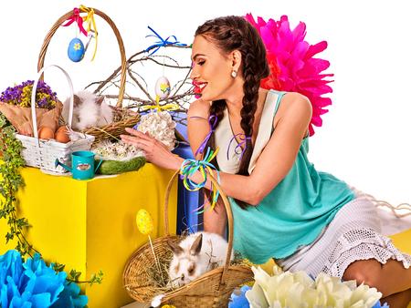 lapin sexy: Pâques jeune fille tenant lapin et les ?ufs. le style de vacances tenue et groupe de lapins dans le panier avec des fleurs. Isolé. Femme avec boîte cadeau. Fond blanc. Banque d'images