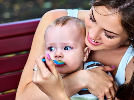 cuillère nourrir bébé par la mère dans l'extérieur du parc. Sevrage en premières semaines. Portrait d'heureux belle maman et enfant été manger sur le banc.