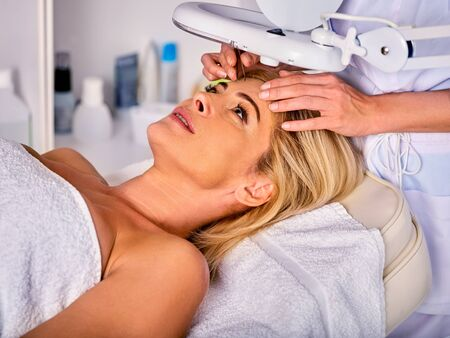 tweezing: Eyebrow treatment of woman middle-aged in spa salon. Tweezing eyebrow by beautician. 40s old female under cosmetic lamp. European facial procedure.
