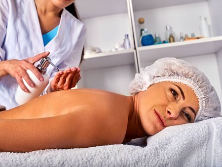 natural therapy: Massage woman therapist making manual therapy back. Hands of masseuse close up. Treatment of spinal injuries 40 old client in spa salon. Beautician uses natural cosmetics. Stock Photo