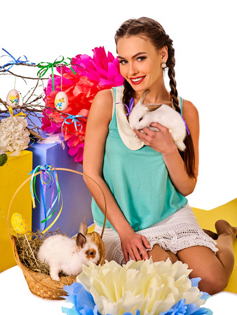 czech women: Easter bunny in girls hands. Decoration egg holding by woman. Holiday style holding and group of rabbits in basket with flowers. Isolated. Young woman with present box at home. White background.