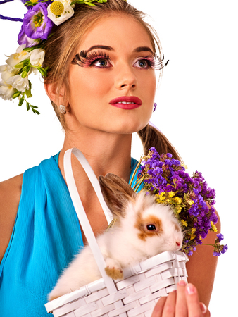 Easter girl holding bunny and eggs. Woman with holiday spring flowers hairstyle and make up holding rabbit in basket . White background. Makeup with fake eyelashes.