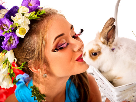 Easter girl holding bunny and eggs. Woman with holiday spring flowers hairstyle and make up kissing rabbit . White background. Makeup with fake eyelashes.