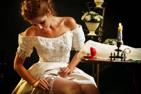 wedding night: Wedding night preparing garter. Bride undressing and put veil on table. Candle illuminates house. Jewelry box next to girl. Baskets of flowers on black background.