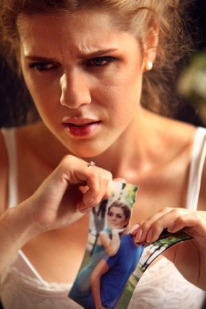 Broken heart woman. Couple break up. Sad bride on unhappy wedding. Woman and groom quarrel. Girl in white dress tearing family pictures. Portrait crying female.