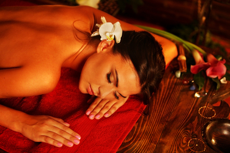 relax massage: Massage of woman in spa salon. Girl on candles background in massage spa salon. Luxary interior in oriental therapy salon. Top view of female have relax after sports training.