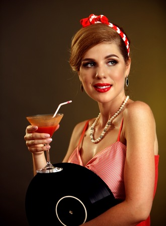 Retro woman with music vinyl record. Pin up girl drink martini cocktail . Pin-up retro female style. Girl pin-up style wearing red dress