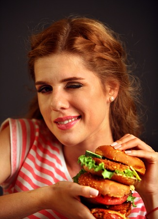 beefburger: Woman eating burger and winks. Happy student going to seductively eat great sandwich for lunch. Joyful woman offers fast food on black background.