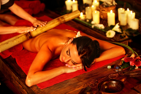 relax massage: Bamboo massage of woman in spa salon. Girl on candles background in massage spa salon. Luxary interior in oriental therapy salon. Female have relax after sport.