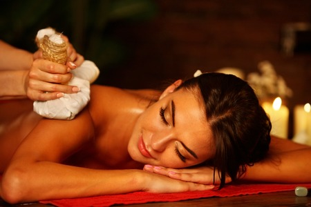 uomo rosso: Massage of woman in spa salon. Girl on candles background in massage spa salon. Luxary interior in oriental therapy salon. Close up of female massage hands give herbs hot ball therapy.