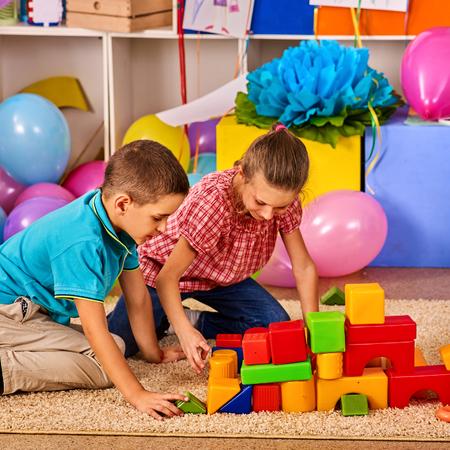 Los niños que juegan en el club de niños de interior. Lección en la escuela primaria. Niño y niña junto juegan. Jardín de infancia el niño se sienta en el suelo con globo