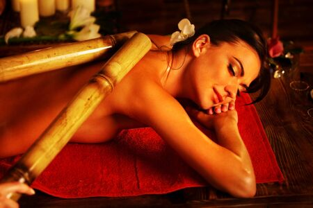 relax massage: Bamboo massage of woman in spa salon. Girl on candles background in massage spa salon. Luxary interior in oriental therapy salon. Female have relax big stick after sport on red towel.