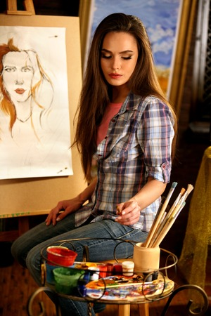 Artist painting on easel in studio. Girl paints portrait of woman with brush. Female painter seen from behind. She thinks about choice of brushes. Indoor home interior for handmade crafts. Stock Photo